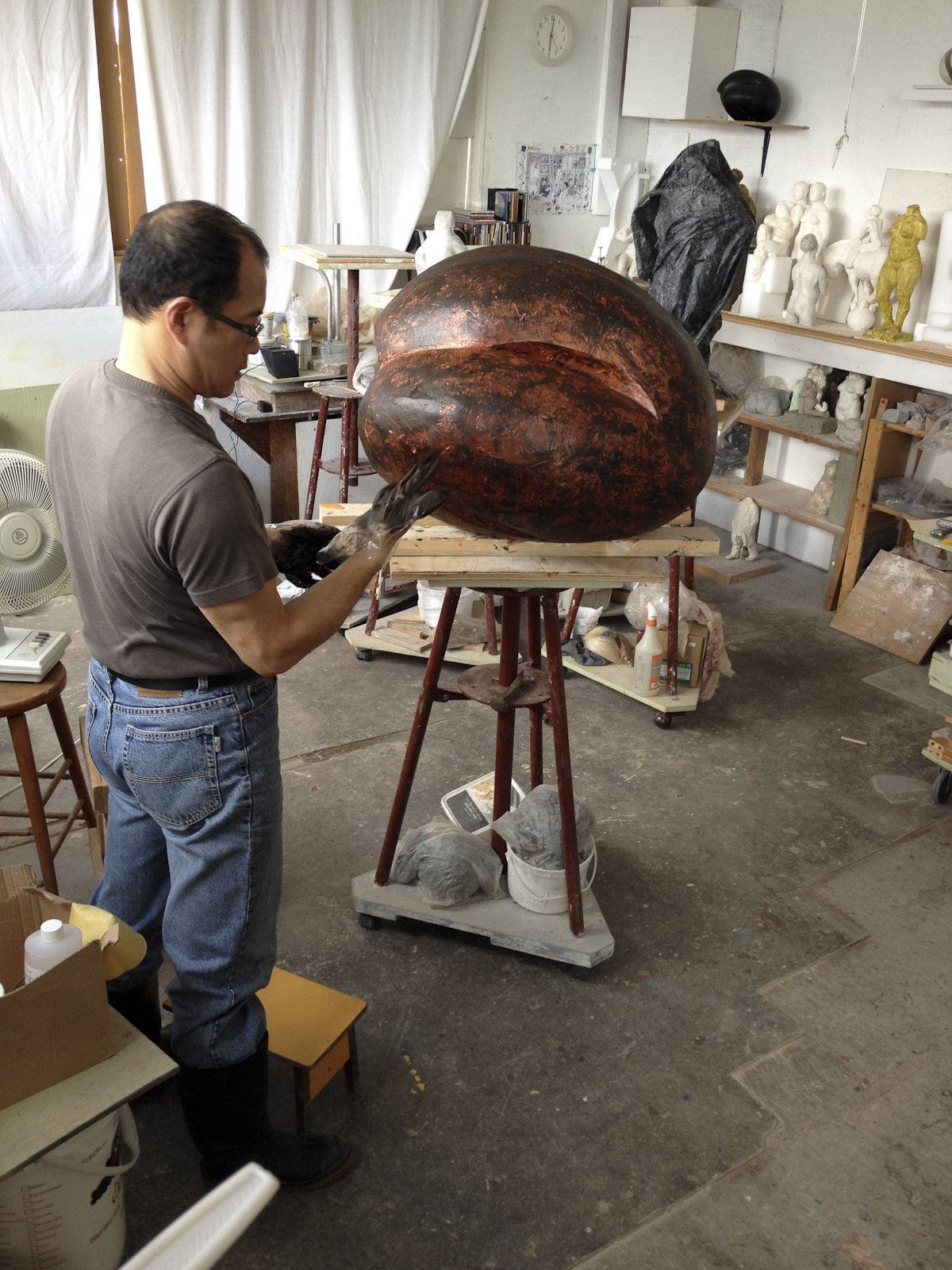 sculptor at work in studio on abstract sculpture